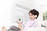 イヤホンをしながら雑誌を読む女性