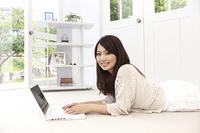 寝転がりパソコンを使用する女性