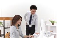 パソコンを見つめ会話するビジネスマンとビジネスウーマン