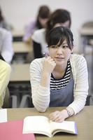 授業中頬杖をつく女子学生
