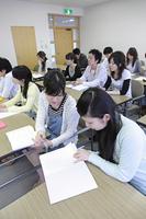 授業の内容を確認する女子学生