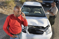 Man with police officer on mobile phone following car accident
