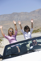 Women in convertible with hands raised