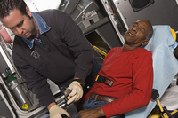 Paramedic helping man in ambulance