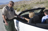 female driver hands papers to police officer