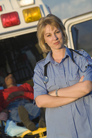 Paramedic stands with arms folded near ambulance