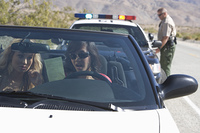 Young woman drive convertible police officer stands at his car