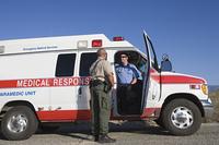 Policeman talks to paramedic at vehicle