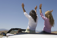 Women with hands raised in the back of a convertible