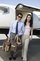 Portrait of mid-adult Asian business couple standing in front of private airplane.