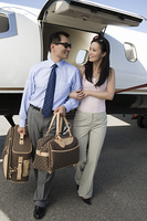 Mid-adult Asian business couple walking in front of private airplane.