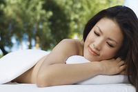 Young woman lying on massage table outdoors