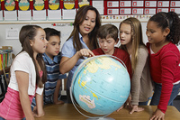 Group of pupils and teacher looking at the globe