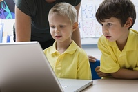 Two schoolboys sit learning computer technology