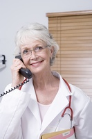 Senior healthcare professional holds telephone receiver