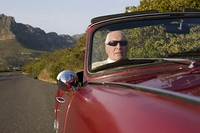 Senior man in vintage racing car on Signal Hill  Cape Town  South Africa