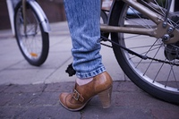 The bottom half of a bicycle and a ladies leg