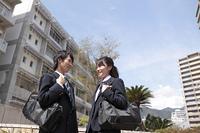 学校の前で会話をしている高校生