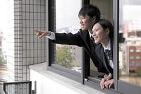 窓から顔を出す男子高生と女子高生