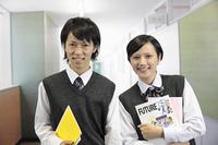 学校の廊下 教科書を抱える男子高生と女子高生