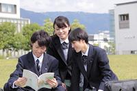 芝生に座り教科書を読む高校生たち