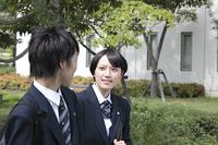 会話をしながら登校する男子高生と女子高生