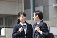 校門の前で話しをする女子高生