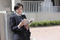 校門の前で教科書を開く女子高生