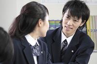 前の席の女の子と話しをする男子高生