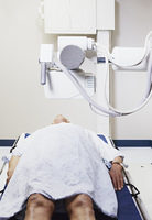 Elderly man in gown lay on x-ray table