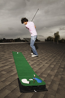 Young man playing miniature golf on roof