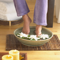 Woman soaking her feet in a bowl of water