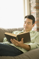 Young man reading on the couch
