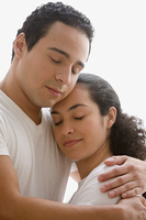 Studio shot of Hispanic couple hugging with their eyes closed