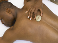 Young man having a hot rock massage