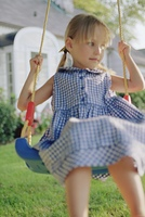 Young girl on swing in yard