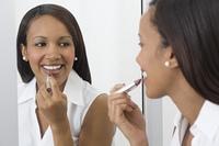 African woman applying lipstick in mirror