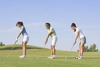 Three women playing golf