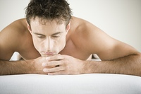 Close up of man with bare shoulders laying on stomach