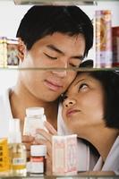 Portrait of Asian couple through medicine cabinet