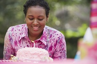 African woman blowing out birthday candle
