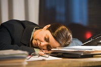 Hispanic businesswoman sleeping on desk