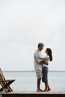 South American couple hugging on dock