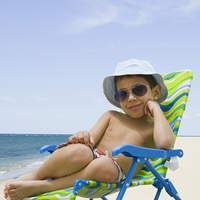 Hispanic boy sitting in beach chair
