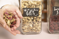Chinese medicinal herbs in jars and cupped hands