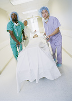 Healthcare workers wheeling man on bed
