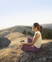 Middle-aged woman meditating outdoors