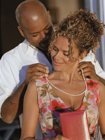 African American man putting necklace on African American woman