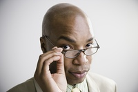 African businessman with hand on eyeglasses