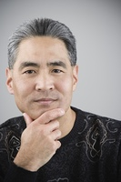 Asian man with hand on chin